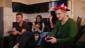Παίζοντας παιχνίδι νεαρών άνδρων δύο ενώ οι φίλες τους που μιλούν πέρα από το παιχνίδι απόθεμα βίντεο