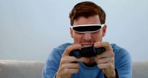 Παίζοντας παιχνίδι πηδαλίων ατόμων με την κάσκα εικονικής πραγματικότητας στον καναπέ 4k φιλμ μικρού μήκους