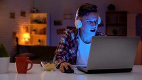 Παίζοντας παιχνίδι στον υπολογιστή εφήβων Overemotional στο lap-top και την κατανάλωση των πρόχειρων φαγητών, εθισμός στοκ φωτογραφία