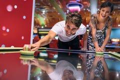 Παίζοντας παιχνίδι χόκεϋ αέρα ζεύγους σε ένα τυχερό παιχνίδι arcade στοκ εικόνα
