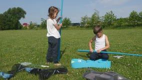 Παίζοντας παιχνίδι αδελφών και αδελφών παιδιών στη χλόη απόθεμα βίντεο