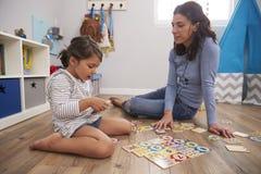 Παίζοντας παιχνίδι γρίφων αριθμού μητέρων με την κόρη στο χώρο για παιχνίδη Στοκ εικόνα με δικαίωμα ελεύθερης χρήσης