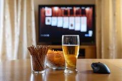 Παίζοντας παιχνίδι καρτών στη μεγάλη οθόνη TV με το snacks&alcohol στοκ εικόνες