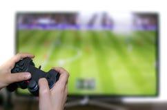 Παίζοντας ποδόσφαιρο αγοριών στην τηλεοπτική οθόνη με την κονσόλα παιχνιδιών στοκ εικόνα