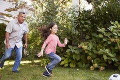 Παίζοντας ποδόσφαιρο παππούδων στον κήπο με την εγγονή στοκ φωτογραφία