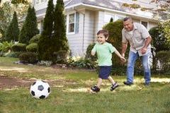 Παίζοντας ποδόσφαιρο παππούδων στον κήπο με τον εγγονό στοκ φωτογραφίες με δικαίωμα ελεύθερης χρήσης