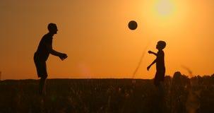 Παίζοντας ποδόσφαιρο πατέρων και γιων στο πάρκο στο ηλιοβασίλεμα, σκιαγραφίες ενάντια στο σκηνικό ενός φωτεινού ήλιου, σε αργή κί απόθεμα βίντεο
