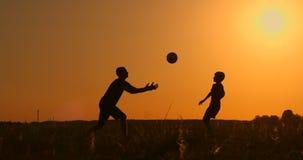 Παίζοντας ποδόσφαιρο πατέρων και γιων στο πάρκο στο ηλιοβασίλεμα, σκιαγραφίες ενάντια στο σκηνικό ενός φωτεινού ήλιου, σε αργή κί φιλμ μικρού μήκους