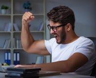 Παίζοντας πολλές ώρες παιχνιδιών νεαρών άνδρων αργά στο γραφείο στοκ εικόνες