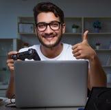 Παίζοντας πολλές ώρες παιχνιδιών νεαρών άνδρων αργά στο γραφείο στοκ εικόνα