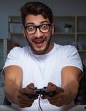 Παίζοντας πολλές ώρες παιχνιδιών νεαρών άνδρων αργά στο γραφείο στοκ φωτογραφία με δικαίωμα ελεύθερης χρήσης