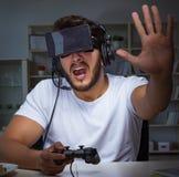 Παίζοντας πολλές ώρες παιχνιδιών νεαρών άνδρων αργά στο γραφείο στοκ εικόνα με δικαίωμα ελεύθερης χρήσης