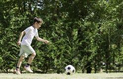 Παίζοντας ποδόσφαιρο παιδιών σε ένα στάδιο Στοκ Εικόνες