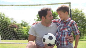 Παίζοντας ποδόσφαιρο πατέρων και γιων στον κήπο στο σπίτι απόθεμα βίντεο