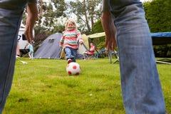 Παίζοντας ποδόσφαιρο πατέρων και κορών στον κήπο από κοινού στοκ εικόνα με δικαίωμα ελεύθερης χρήσης