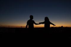 Παίζοντας σενάριο ζευγών σκιαγραφιών στο ηλιοβασίλεμα Στοκ Εικόνα