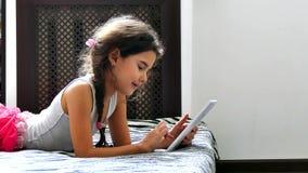 Παίζοντας συνεδρίαση Διαδικτύου παιχνιδιών ταμπλετών εφήβων κοριτσιών στο κρεβάτι φιλμ μικρού μήκους
