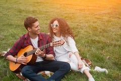 Παίζοντας συνεδρίαση κιθάρων τύπων με το κορίτσι Στοκ φωτογραφία με δικαίωμα ελεύθερης χρήσης