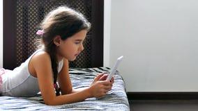 Παίζοντας συνεδρίαση παιχνιδιών Διαδικτύου ταμπλετών εφήβων κοριτσιών στο κρεβάτι απόθεμα βίντεο