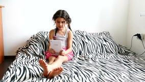 Παίζοντας συνεδρίαση ταμπλετών κοριτσιών εφήβων στο κρεβάτι φιλμ μικρού μήκους