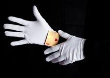 Παίζοντας τέχνασμα καρτών με τα χέρια άσσων με τα γάντια στοκ εικόνα