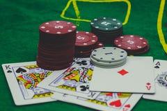 παίζοντας τις κάρτες, χωρίζει σε τετράγωνα και πόκερ τσιπ άνωθεν στο πράσινο πόκερ Στοκ Φωτογραφίες