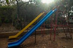 παίζοντας φωτογραφικές διαφάνειες για τα παιδιά σε ένα δημόσιο πάρκο στοκ εικόνες