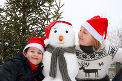 Παίζοντας χιονάνθρωπος μητέρων και γιων Στοκ εικόνα με δικαίωμα ελεύθερης χρήσης