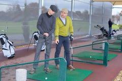 Παίκτες γκολφ που ασκούν να τοποθετήσει στο σημείο αφετηρίας μακριά Στοκ Εικόνες
