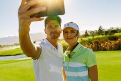 Παίκτες γκολφ που παίρνουν selfie με το κινητό τηλέφωνο Στοκ Εικόνες