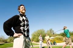 Παίκτες γκολφ που προσέχουν άλλο παίκτη γκολφ στο σημείο αφετηρίας μακριά Στοκ Εικόνες