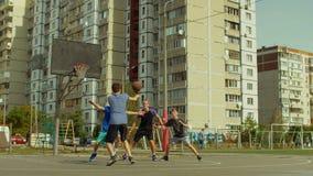 Παίκτες εφήβων streetball που παίζουν το παιχνίδι καλαθοσφαίρισης φιλμ μικρού μήκους
