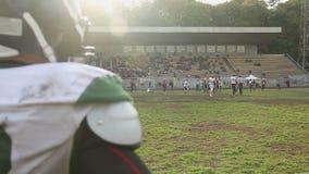 Παίκτες και υποστηρικτές επιφύλαξης που προσέχουν την επίθεση στο ερασιτεχνικό παιχνίδι αμερικανικού ποδοσφαίρου απόθεμα βίντεο