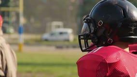 Παίκτες ομάδων αμερικανικού ποδοσφαίρου που ακούνε για να προγυμνάσει τις οδηγίες πριν από το παιχνίδι φιλμ μικρού μήκους