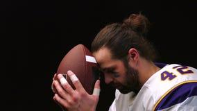Παίκτης αμερικανικού ποδοσφαίρου που κρατούν ήπια και φιλούν τη σφαίρα του και διαβάζουν διανοητικά μια προσευχή πριν από την αντ απόθεμα βίντεο