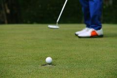 Παίκτης γκολφ που βάζει τη σφαίρα γκολφ στο πράσινο γκολφ Στοκ Εικόνες