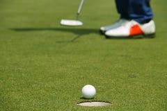 Παίκτης γκολφ που βάζει τη σφαίρα γκολφ στο πράσινο γκολφ Στοκ εικόνες με δικαίωμα ελεύθερης χρήσης