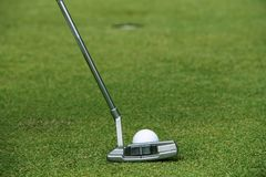 Παίκτης γκολφ που βάζει τη σφαίρα γκολφ στο πράσινο γκολφ Στοκ Φωτογραφίες