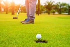 Παίκτης γκολφ που υποβάλλει τη σφαίρα γκολφ στο πράσινο γκολφ, φλόγα φακών στον καθορισμένο χρόνο βραδιού ήλιων, υπέρ σφαίρα γκολ στοκ εικόνες