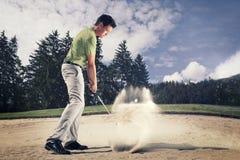 Παίκτης γκολφ στην παγίδα άμμου. Στοκ Φωτογραφία