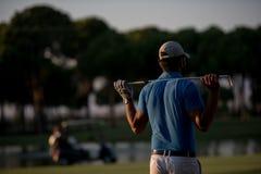 Παίκτης γκολφ από πίσω στη σειρά μαθημάτων που κοιτάζει στην τρύπα στην απόσταση Στοκ φωτογραφία με δικαίωμα ελεύθερης χρήσης