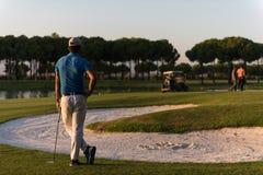 Παίκτης γκολφ από πίσω στη σειρά μαθημάτων που κοιτάζει στην τρύπα στην απόσταση Στοκ Εικόνες