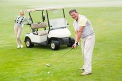 Παίκτης γκολφ για να τοποθετήσει στο σημείο αφετηρίας περίπου μακριά με το συνεργάτη πίσω από τον Στοκ Εικόνες