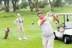 Παίκτης γκολφ για να τοποθετήσει στο σημείο αφετηρίας περίπου μακριά με το συνεργάτη πίσω από τον Στοκ Φωτογραφία