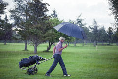 Παίκτης γκολφ μια βροχερή ημέρα που αφήνει το γήπεδο του γκολφ στοκ εικόνα