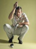 Παίκτης γκολφ που κάθεται οκλαδόν με τη λέσχη και τη σφαίρα Στοκ Φωτογραφίες