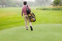 Παίκτης γκολφ που περπατά μακριά το κράτημα της τσάντας γκολφ Στοκ εικόνα με δικαίωμα ελεύθερης χρήσης