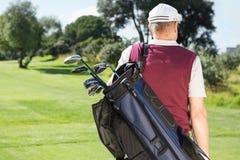 Παίκτης γκολφ που φέρνει την τσάντα γκολφ του Στοκ Φωτογραφία