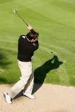 Παίκτης γκολφ που χτυπά τη σφαίρα γκολφ από μια παγίδα άμμου Στοκ Εικόνες