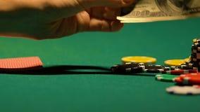 Παίκτης πόκερ που βάζει τα μετρητά δολαρίων κοντά στα τσιπ χαρτοπαικτικών λεσχών, παράνομο παιχνίδι, τελευταία χρήματα απόθεμα βίντεο